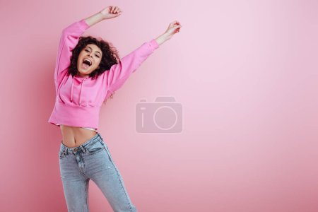 happy bi-racial girl looking at camera while standing with raised hands on pink background