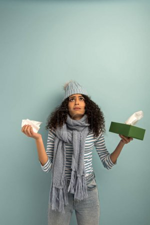 Photo for Diseased bi-racial girl in warm hat and scarf looking up while holding paper napkins on grey background - Royalty Free Image