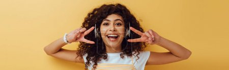 Photo for Panoramic shot of excited mixed race girl in wireless headphones showing victory gesture on yellow background - Royalty Free Image