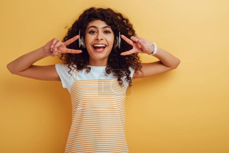 Photo for Cheerful mixed race girl in wireless headphones showing victory gesture on yellow background - Royalty Free Image