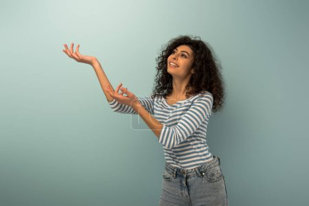 Photo for Smiling bi-racial girl looking up while standing with outstretched hands on grey background - Royalty Free Image