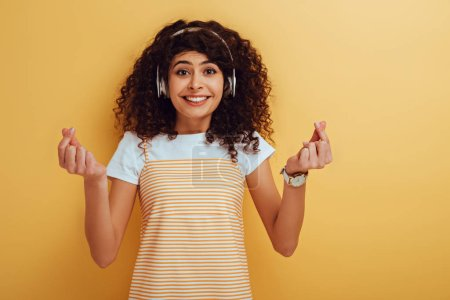Photo for Excited mixed race girl in wireless headphones showing winner gesture on yellow background - Royalty Free Image