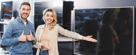 Photo pour Plan panoramique de petit ami montrant aime et souriant petite amie pointant avec la main à la nouvelle télévision dans le magasin d'appareils ménagers - image libre de droit