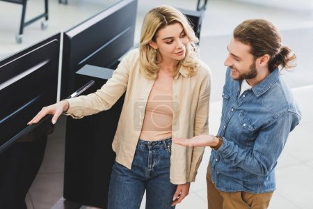 Photo for High angle view of smiling boyfriend pointing with hand at new tv and talking with girlfriend in home appliance store - Royalty Free Image