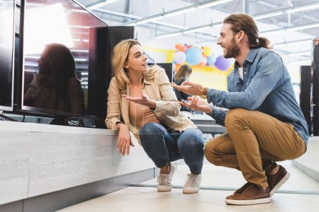 Photo for Smiling boyfriend and girlfriend pointing with hands at new tv and talking in home appliance store - Royalty Free Image