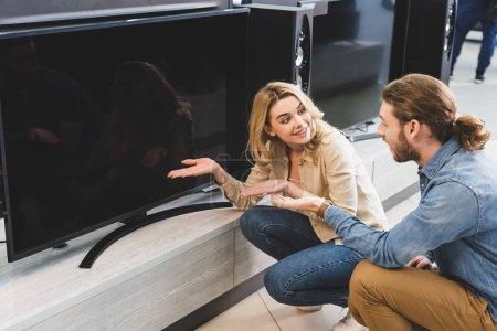 Photo pour Ami et amie souriante pointant les mains vers la nouvelle télévision et parlant dans le magasin d'appareils électroménagers - image libre de droit