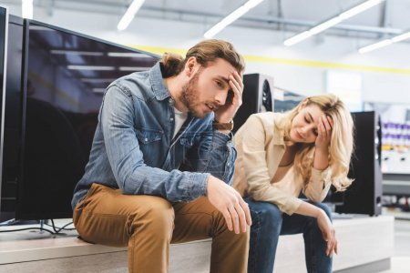 Photo for Sad boyfriend and girlfriend sitting near new tv in home appliance store - Royalty Free Image