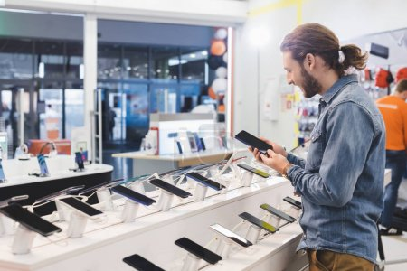 Photo for Side view of smiling man holding smartphone in home appliance store - Royalty Free Image