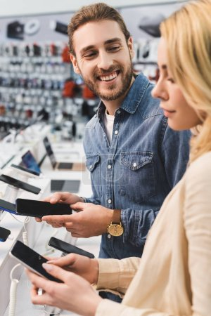 Photo for Selective focus of smiling boyfriend looking at girlfriend with new smartphone in home appliance store - Royalty Free Image