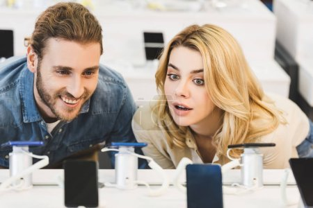 Photo for Smiling boyfriend and shocked girlfriend looking at new smartphones in home appliance store - Royalty Free Image