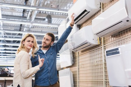 Photo for Boyfriend pointing with hand at air conditioner and girlfriend showing no gesture in home appliance store - Royalty Free Image