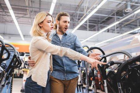 Photo pour Un ami et une amie choqués pointent du doigt un nouvel aspirateur dans un magasin d'appareils électroménagers - image libre de droit