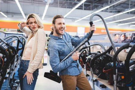 Photo pour Copain jouer avec aspirateur et petite amie montrant signe de paix dans le magasin d'appareils ménagers - image libre de droit