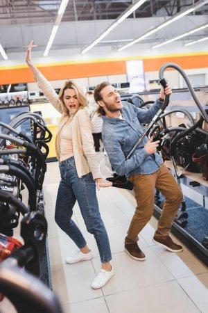 Photo pour Petit ami jouant avec un aspirateur et petite amie dansant et chantant dans un magasin d'appareils électroménagers - image libre de droit