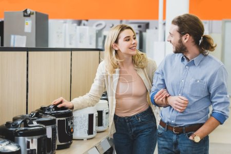 Photo for Smiling consultant and woman talking near slow cookers in home appliance store - Royalty Free Image