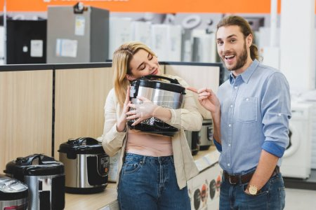 Photo for Smiling consultant pointing with finger at woman with slow cooker in home appliance store - Royalty Free Image