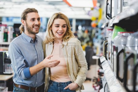 smiling consultant pointing with finger at microwave and talking with woman in home appliance store