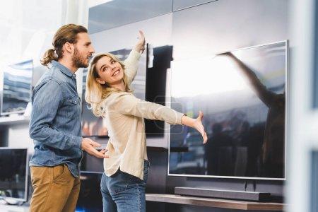 Photo pour Petite amie souriante pointant avec les mains à la télévision et regardant petit ami choqué dans le magasin d'appareils ménagers - image libre de droit