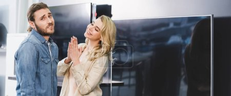 Photo pour Plan panoramique de petit ami confus montrant geste haussement d'épaules et petite amie souriante montrant s'il vous plaît geste près de la télévision dans le magasin d'appareils ménagers - image libre de droit