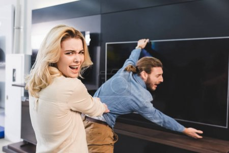 Photo for Selective focus of angry girlfriend pulling boyfriend with tv in home appliance store - Royalty Free Image