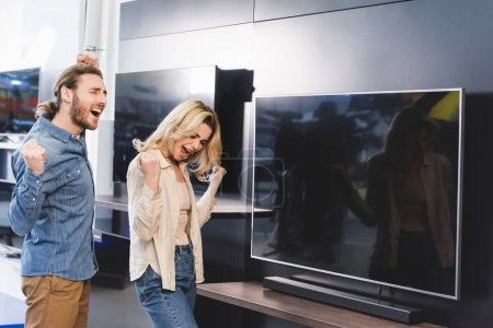 Photo pour Happy boyfriend and girlfriend showing yes gesture near tv in home appliance store - image libre de droit
