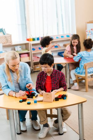 Photo pour Enfants jouant à des jeux de construction par un enseignant avec des enfants en arrière-plan à l'école montessori - image libre de droit