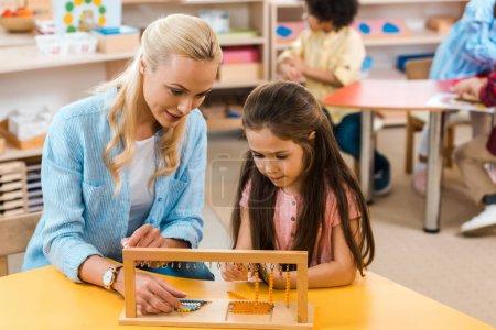 Foto de Enfoque selectivo de niños y maestros que juegan al juego de madera con niños de fondo en la escuela montessori. - Imagen libre de derechos