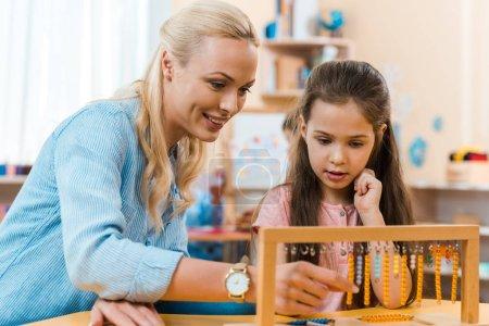 Photo pour Enseignant souriant et enfant jouant au jeu de bois à table dans les classes de montessori - image libre de droit