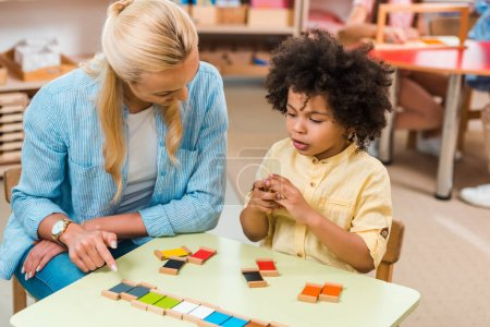 Photo pour Un enfant africain-américain joue à un jeu éducatif par un enseignant à table dans une classe de montessori - image libre de droit
