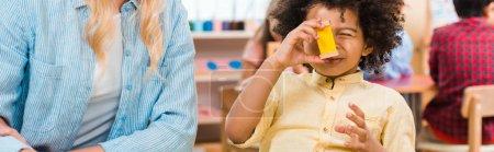Photo pour Photo panoramique d'un enfant jouant à un jeu éducatif par un enseignant de l'école de montessori - image libre de droit