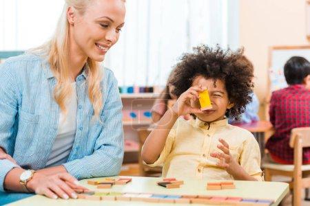 Foto de Enfoque selectivo de profesores sonrientes jugando al juego con niños afriamericanos en clase montessori. - Imagen libre de derechos