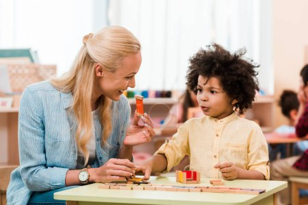 Photo for African american child playing educational game with smiling teacher in montessori school - Royalty Free Image