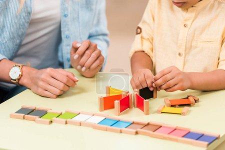Photo pour Vue agrandie d'un enfant et d'un enseignant jouant à un jeu éducatif à table pendant un cours en classe de montessori - image libre de droit