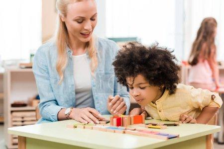 Photo pour Choix sélectif d'un enfant africain d'Amérique jouant à un jeu éducatif avec un enseignant dans une école de montessori - image libre de droit