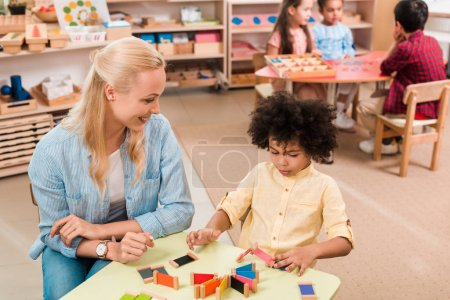 Photo pour Orientation sélective de l'enseignant souriant et de l'enfant avec du jeu de bois à la table et des enfants à l'arrière-plan à l'école montessori - image libre de droit