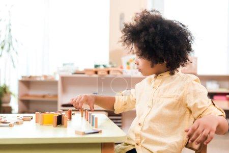 Photo pour Vue latérale de l'enfant afro-américain jouant à la table de l'école montessori - image libre de droit