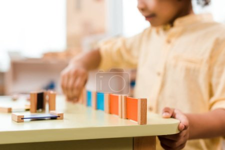 Photo for Selective focus of kid playing educational game in montessori school, cropped view - Royalty Free Image