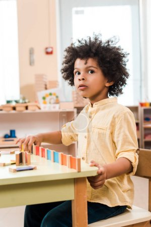 Photo for Pensive african american kid playing wooden game in montessori school - Royalty Free Image