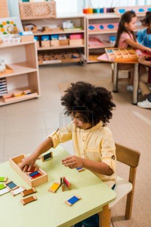 Photo pour Axe sélectif de jeu pour enfants avec des enfants en arrière-plan à l'école montessori - image libre de droit