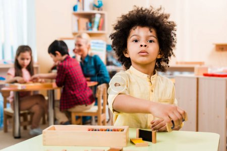 Photo pour Selective focus of african american child with wooden game and teacher with children in montessori school - image libre de droit