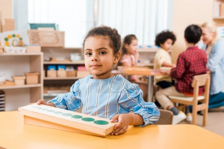 Photo for Selective focus of kid with wooden game looking at camera and teacher with children at background in montessori school - Royalty Free Image