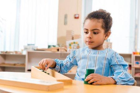 Photo pour Concentration sélective d'un enfant afro-américain jouant à un jeu éducatif en bois à la table de l'école montessori - image libre de droit