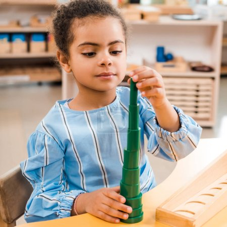 Photo for African american kid playing game during lesson in montessori school - Royalty Free Image