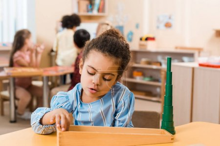 Photo for Selective focus of african american kid playing wooden game at table in montessori school - Royalty Free Image