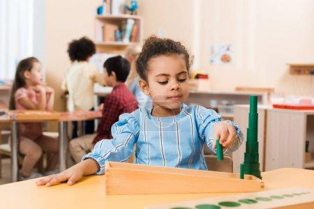 Photo pour Orientation sélective d'un enfant jouant à un jeu éducatif à table avec des enfants à l'arrière-plan dans l'école montessori - image libre de droit