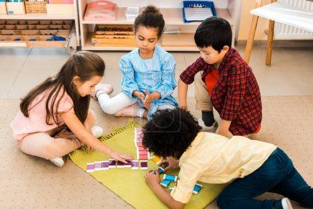 Foto de Vista de gran angular de niños jugando al juego de colores en el suelo durante la clase en la escuela montessori. - Imagen libre de derechos