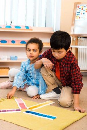 Photo pour Enfants jouant avec un jeu coloré sur un tapis dans une classe de montessori - image libre de droit