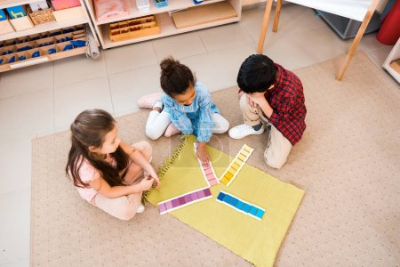 Photo for Overhead view of children playing educational game on floor in montessori class - Royalty Free Image