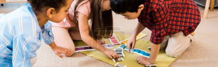 Photo for Panoramic shot of kids playing colorful game on floor in montessori school - Royalty Free Image