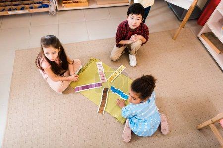 Foto de Vista de gran angular de los niños que juegan en el suelo en la escuela montessori. - Imagen libre de derechos